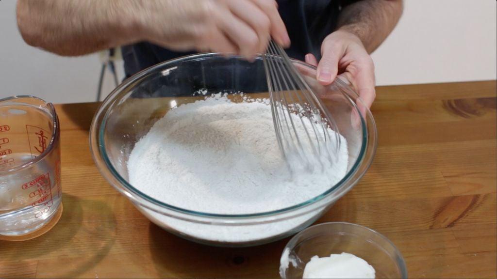 Hand whisking flour, baking powder, salt, in a large glass bowl.