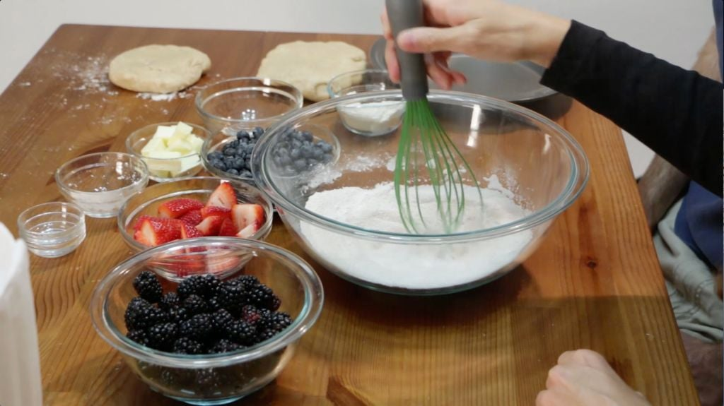 Hand whisking dry pie filling ingredients in a large glass bowl