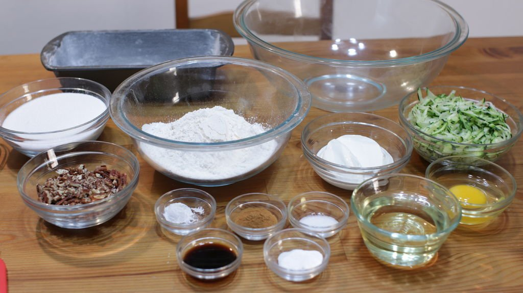 Several ingredients in glass bowls on a table including zucchini, flour, sugar, etc.