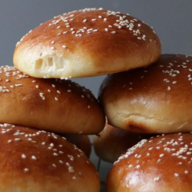 homemade hamburger buns piled up on each other.