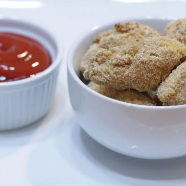 Chicken nuggets in a white bowl next to ketchup