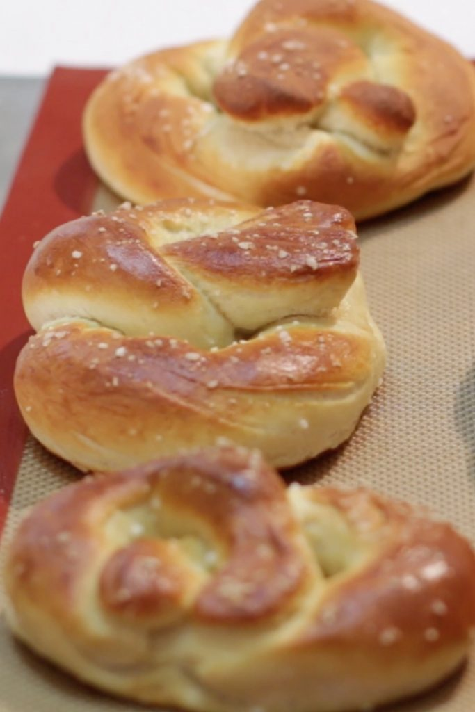 Three homemade soft pretzels freshly baked out of the oven.