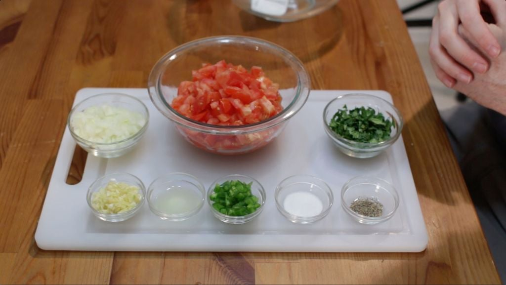 Pico de gallo ingredients in bowls on a white cutting board