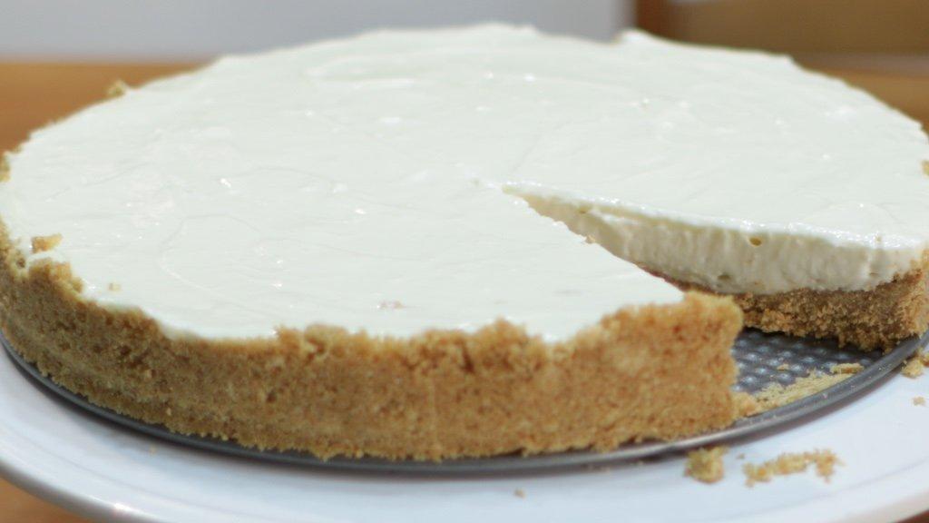 Homemade no-bake cheesecake on a cake pedestal.