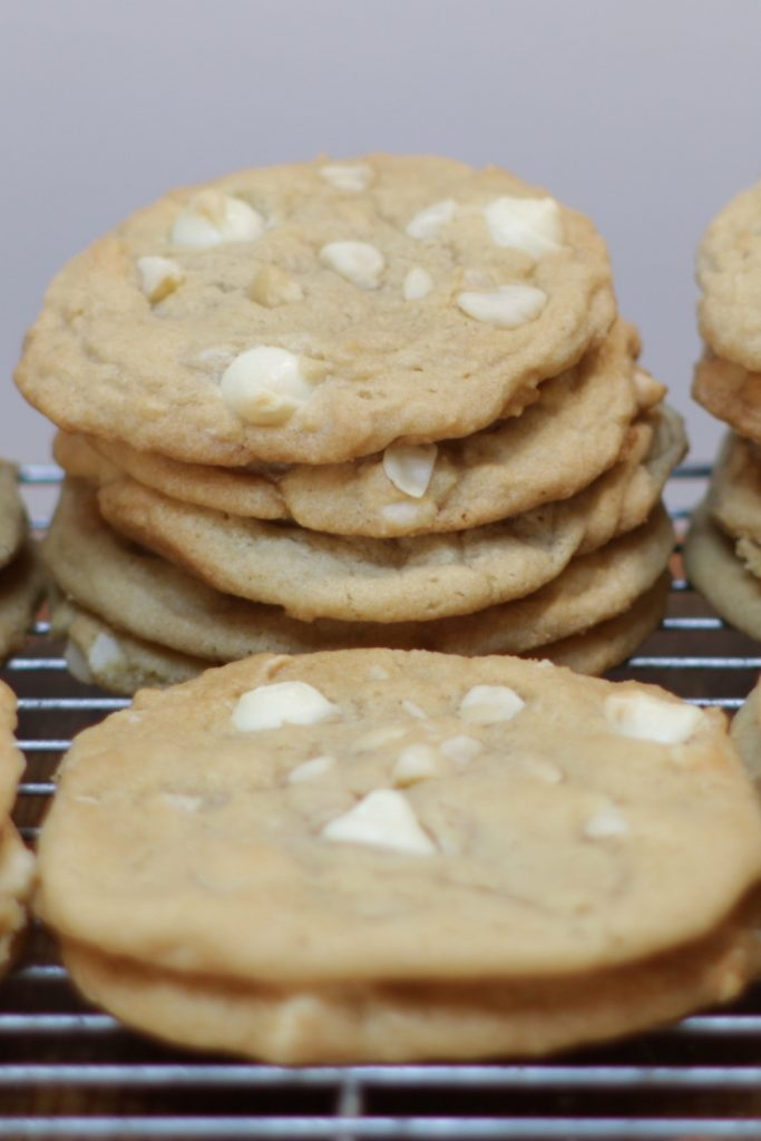 Stacks of fresh homemade white chocolate macadamia nut cookies on a wire rack.