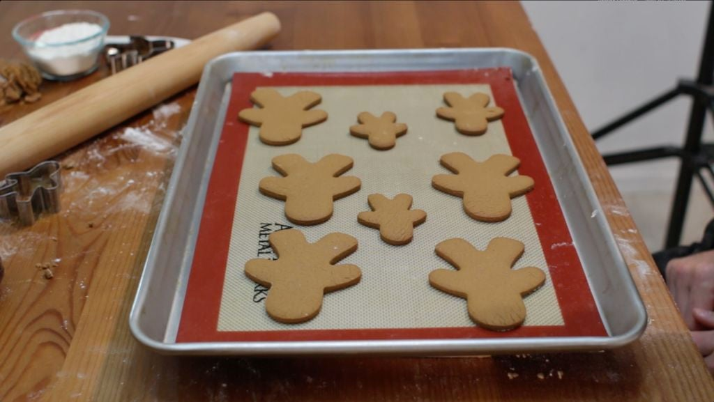 8 freshly baked homemade gingerbread cookies on a sheet pan lined with a silicone mat.