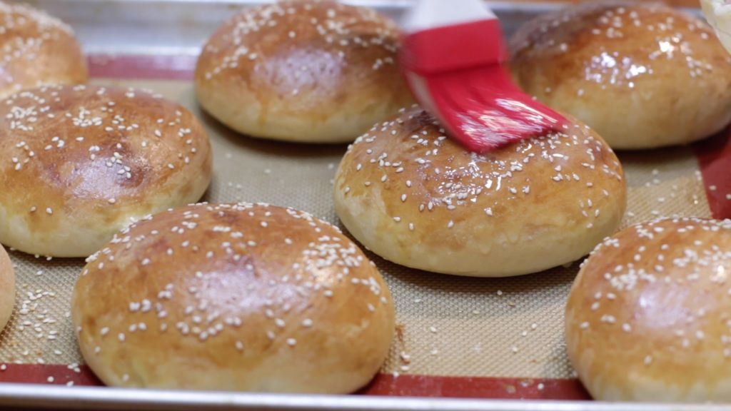 Freshly baked homemade hamburger buns on a sheet pan with a silicone mat.