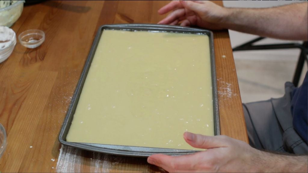 White Texas sheet cake batter in a sheet pan on a wooden table.
