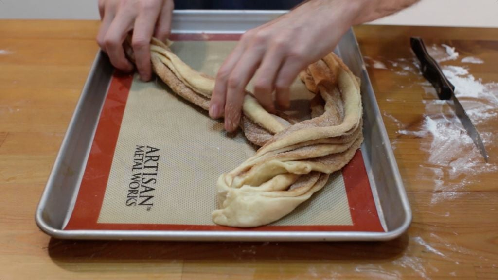 Cinnamon roll twist bread being braided on a sheet pan lined with a silicone mat