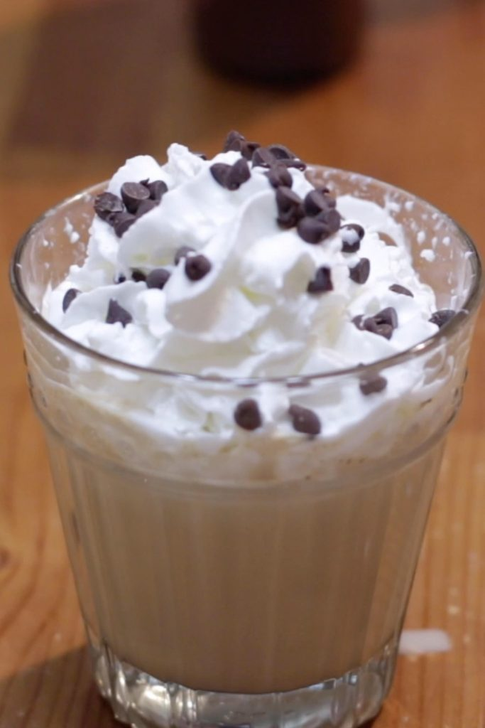 Chocolate milkshake with whipped cream and mini chocolate chips on a wooden table.