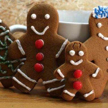 classic ginger bread men cookies standing up on a table.