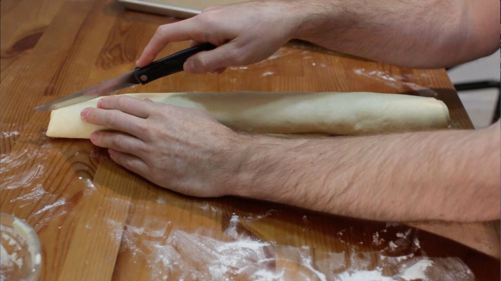 Hand with rolled up cinnamon roll dough.