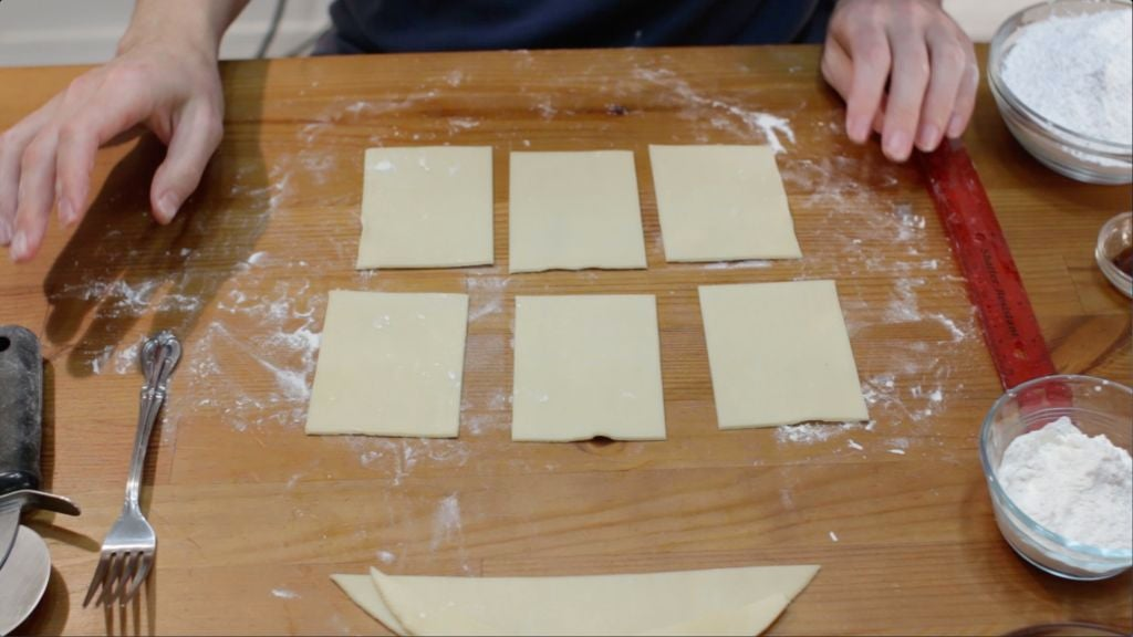 Rectangle cut pieces of pie down on a wooden table.