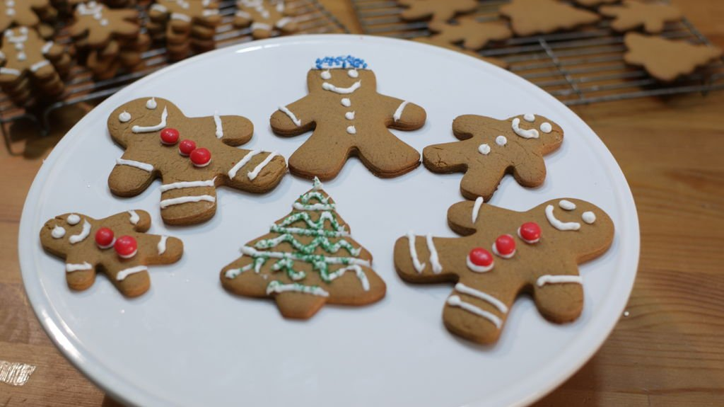 several decorated gingerbread men cookies on a white cake pedestal.