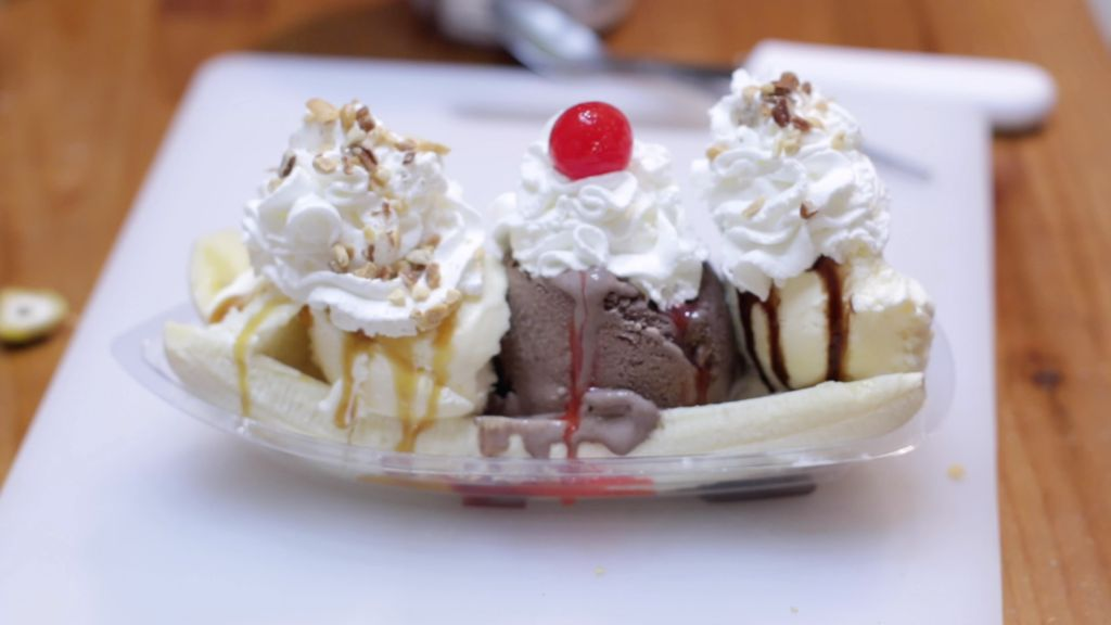 Homemade banana split on a white cutting board.
