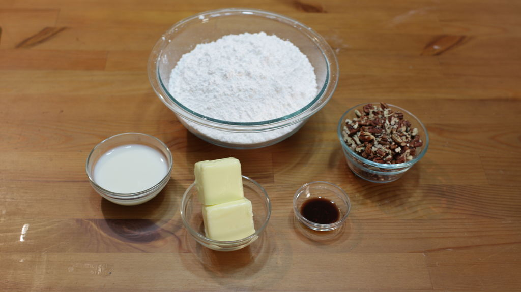 Frosting ingredients, powdered sugar, milk, butter, vanilla extract, and nuts.