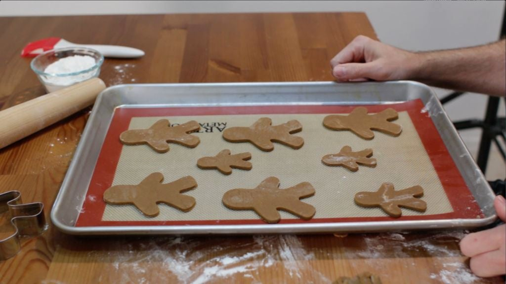 8 gingerbread men on a sheet pan lined with a silicone mat.