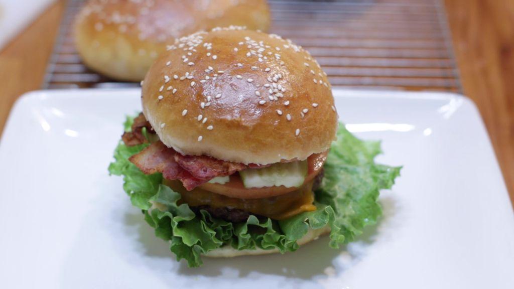 Fresh burger made with a homemade hamburger bun on a white plate.