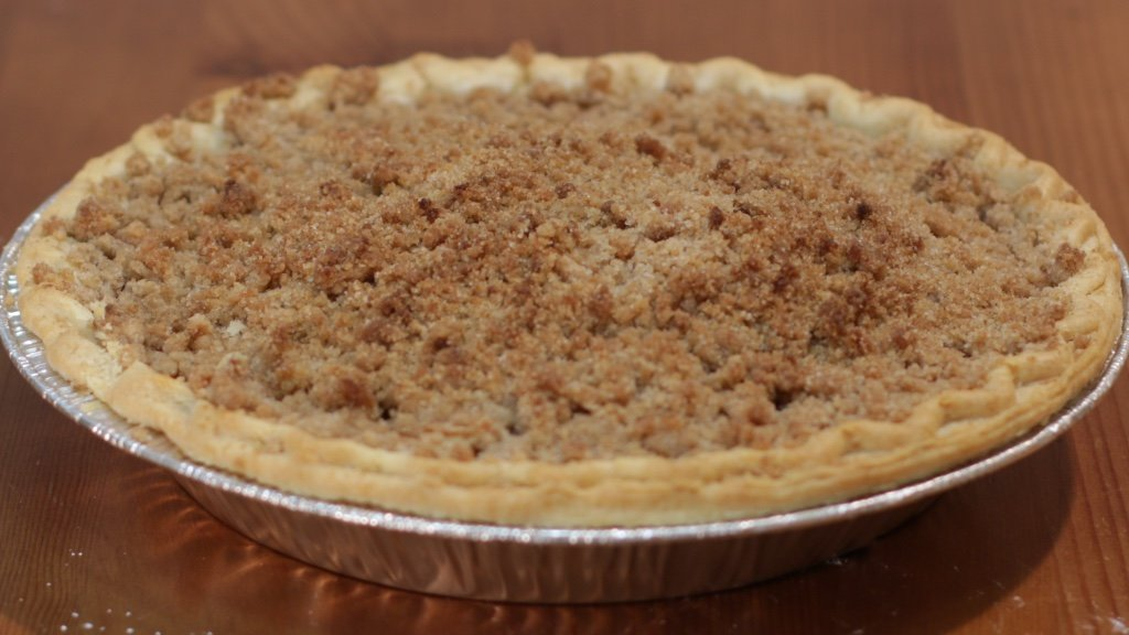 Freshly baked apple crumb pie on a table.