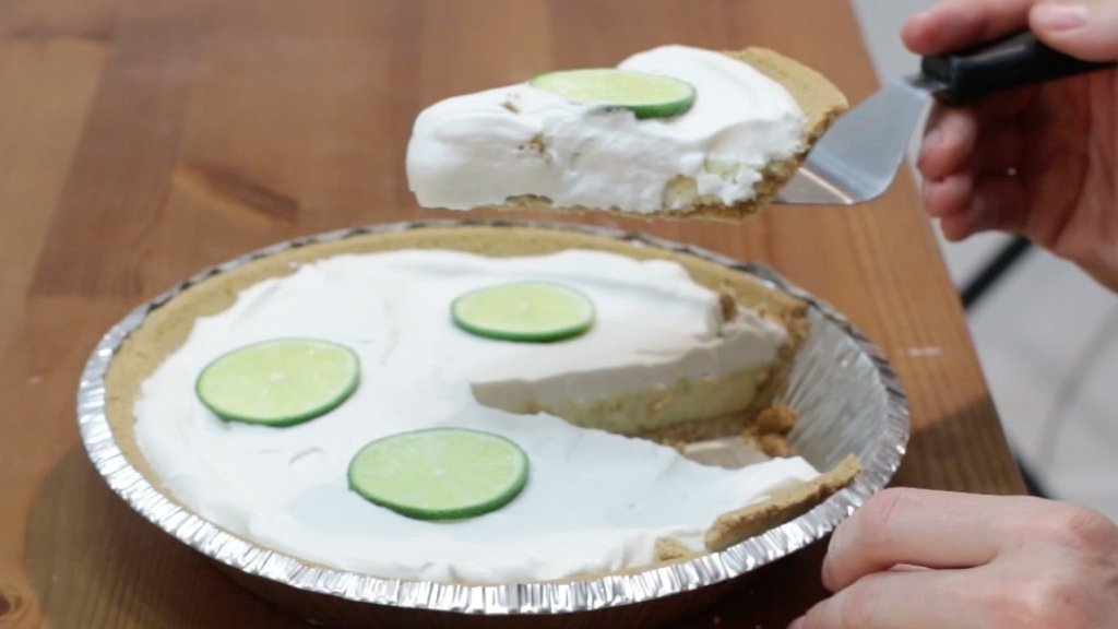 Hand holding a slice of key lime pie above the rest of the pie.