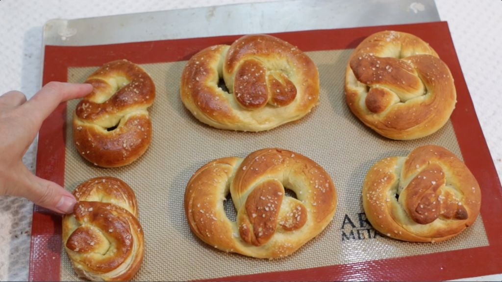 6 baked soft pretzels on a sheet pan with a silicone mat.