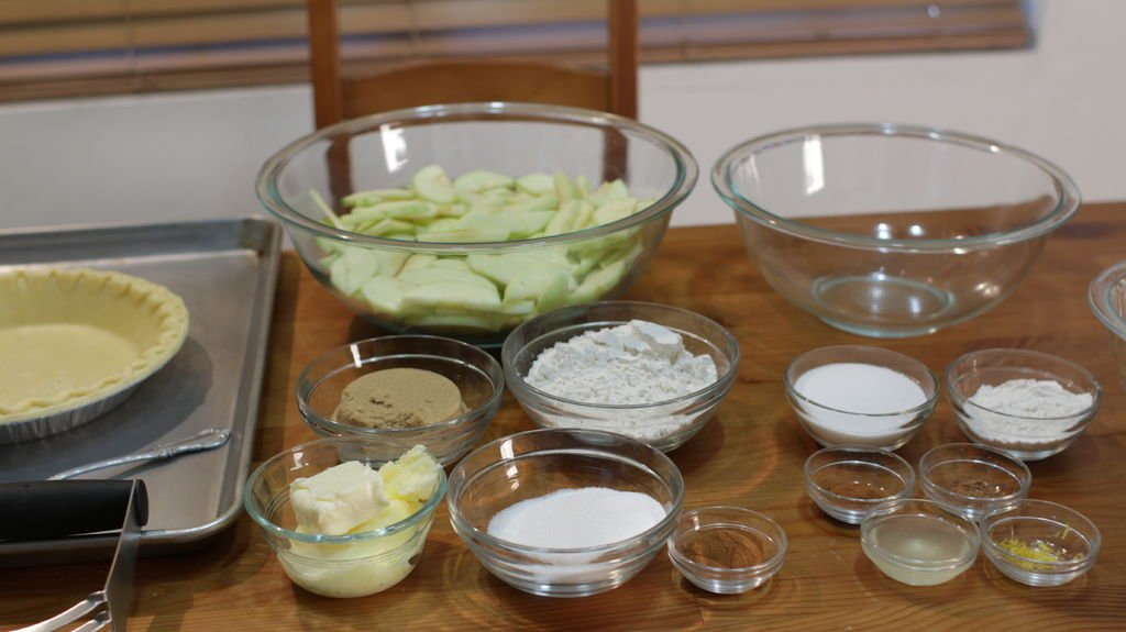 Sliced apples, pie crust, and several other ingredients in glass bowls on a wooden table.