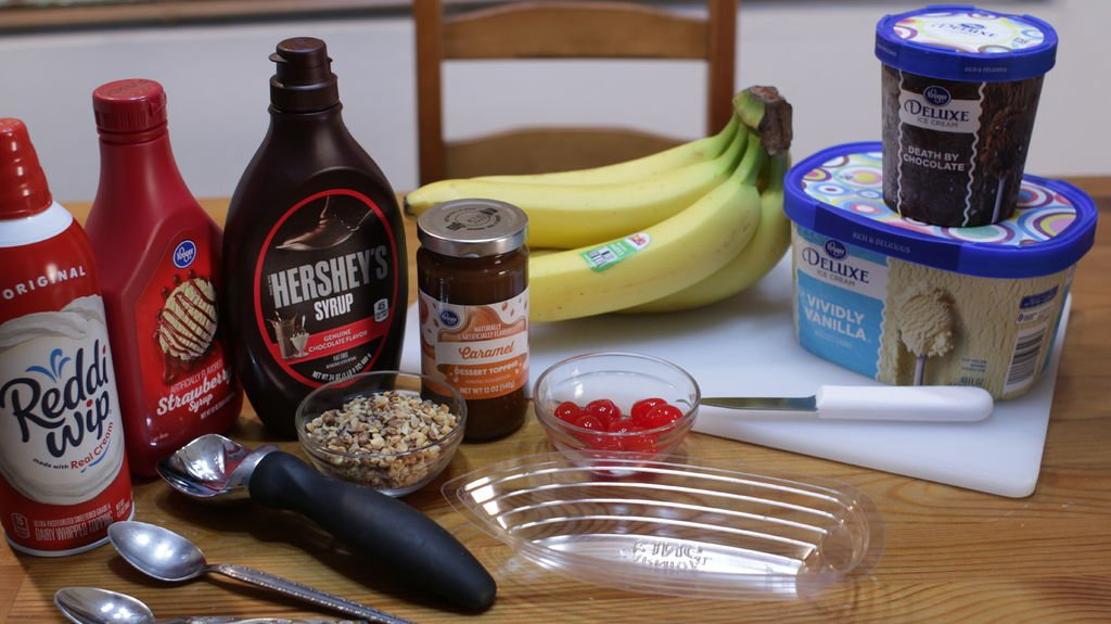 A variety of ingredients on a table including bananas, ice cream, nuts, syrups, etc.