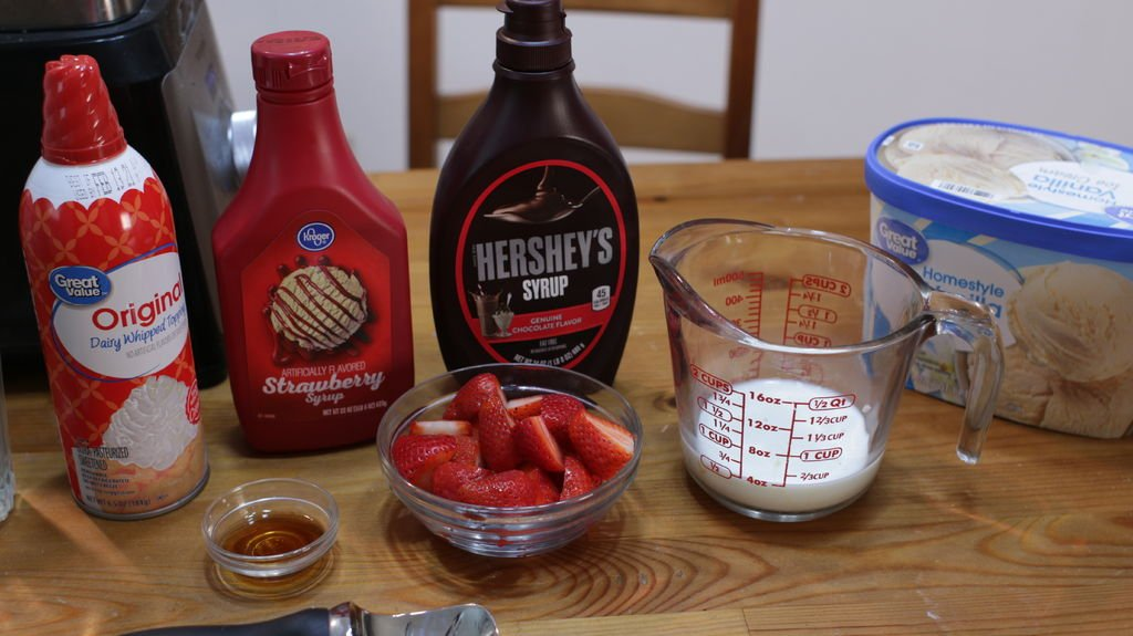 vanilla ice cream, milk, strawberries, chocolate syrup, etc. on a wooden table.