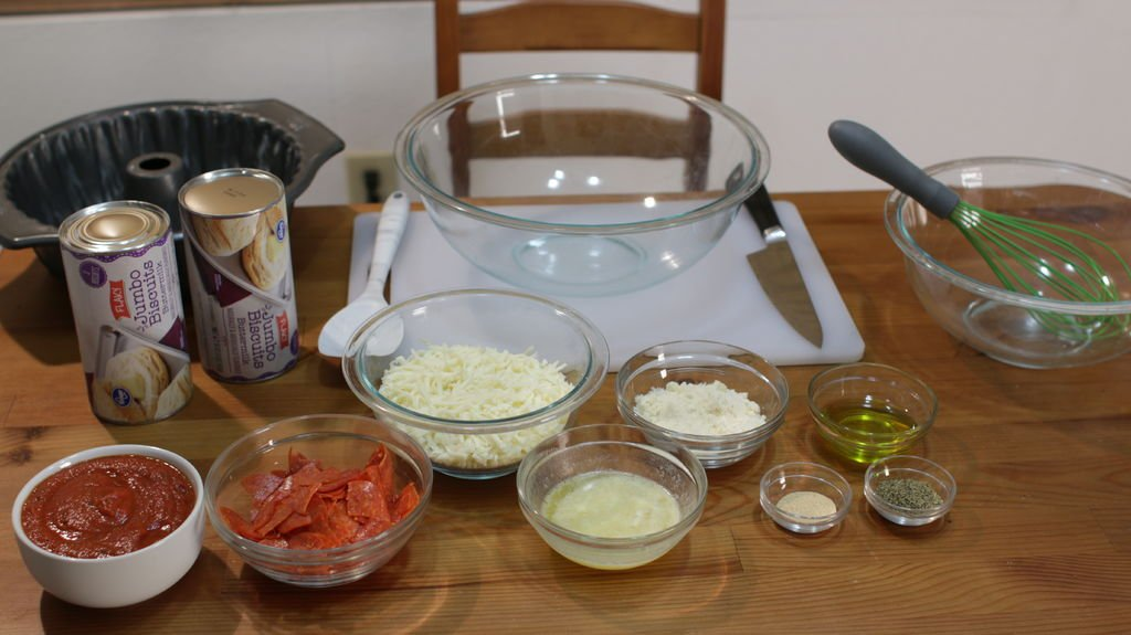 Biscuits, pepperoni, cheese, and other ingredients in glass bowls on a table.