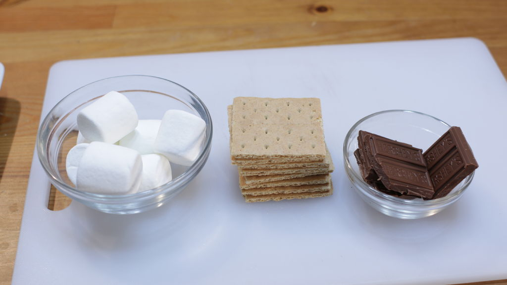 Glass bowls of marshmallows, graham crackers, and Hershey's milk chocolate