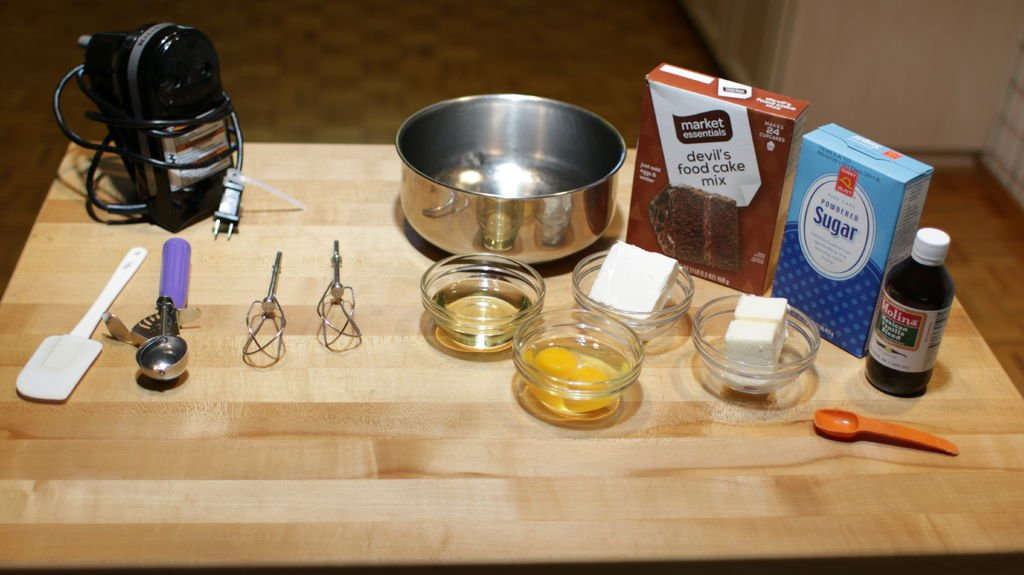 Several ingredients on a wooden table including cake mix, powdered sugar, cream cheese, butter, eggs, etc.