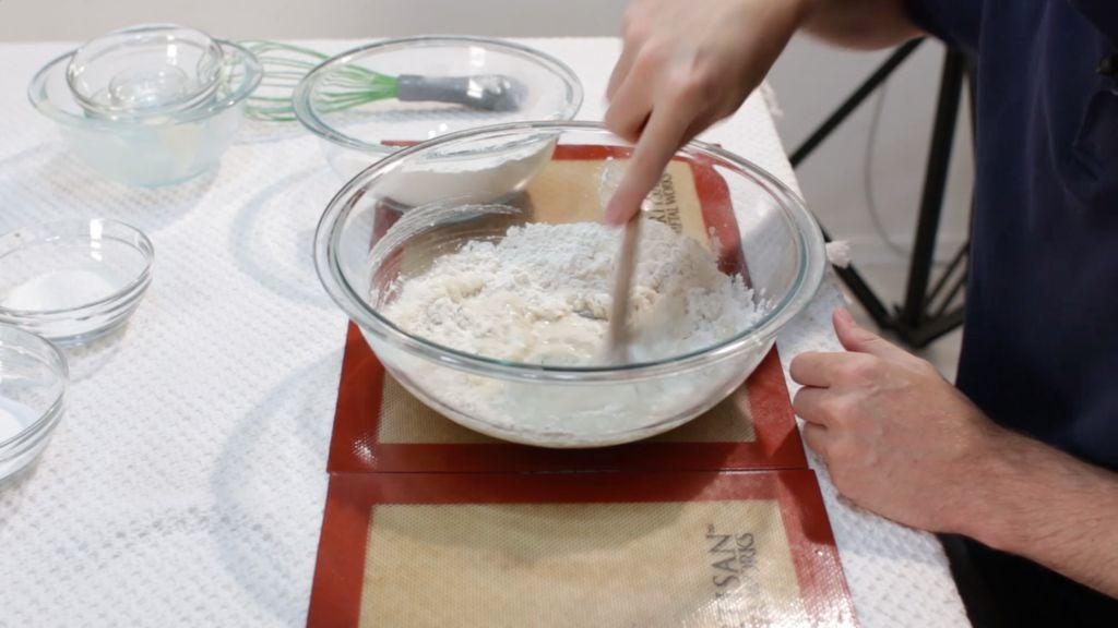 Hand stirring soft pretzels dough in a large bowl.
