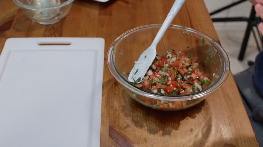 Glass bowl of homemade pico de gallo with a white spatula sitting in it.