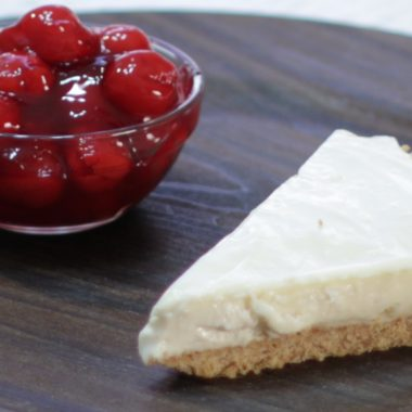 Slice of no-bake cheesecake on a plate next to bowl of cherries