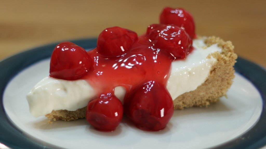 Slice of no-bake cheesecake on a plate with cherries on top.