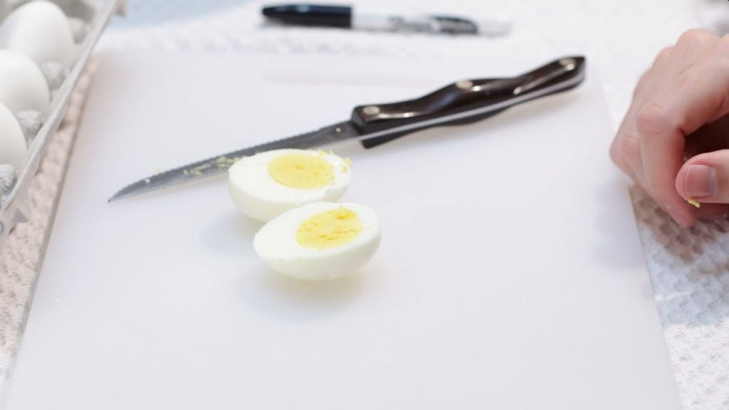 A perfect hard boiled egg cut in half on a white cutting board.