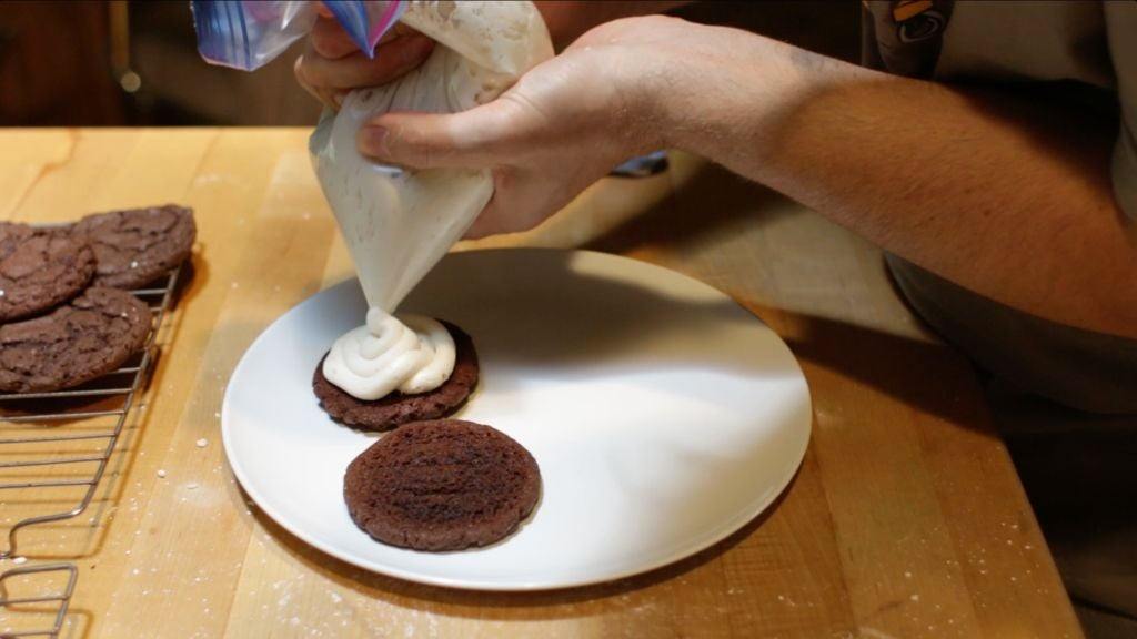 Cream cheese frosting being piped onto a cookie.