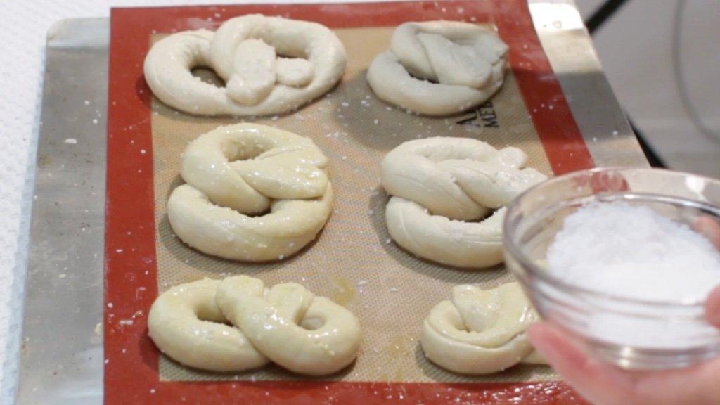 6 unbaked soft pretzels on a sheet pan with kosher salt on top.