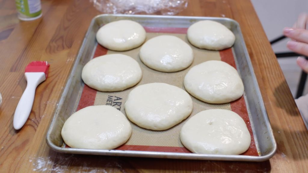 Homemade hamburger buns on a sheet pan lined with a silicone mat.