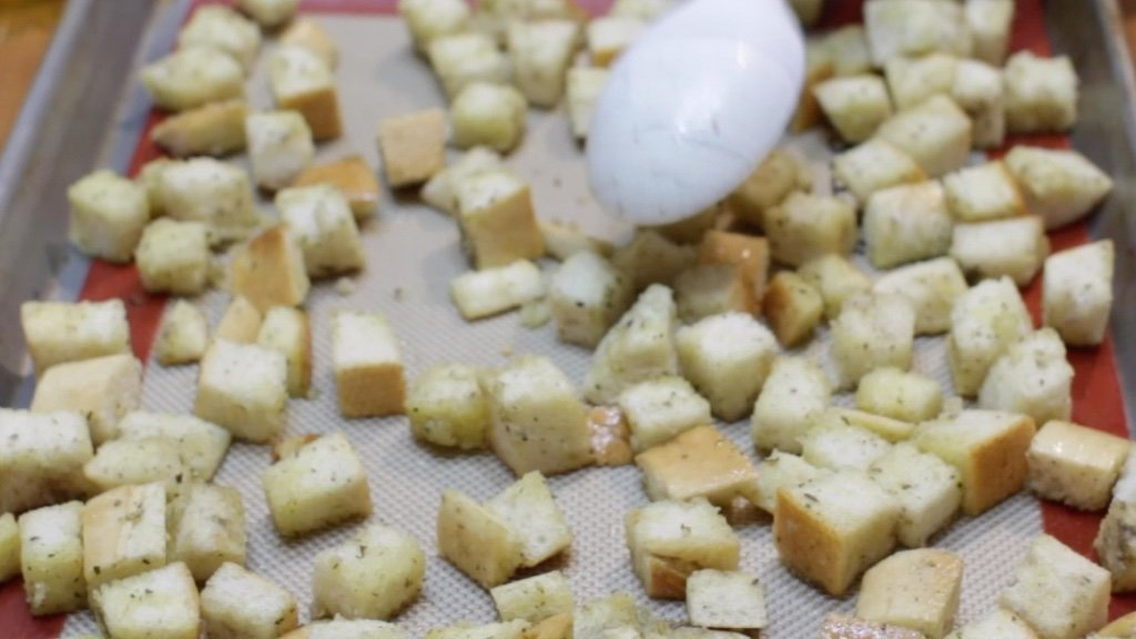 Spoon spread out unbaked croutons onto a sheet pan lined with a silicone mat.