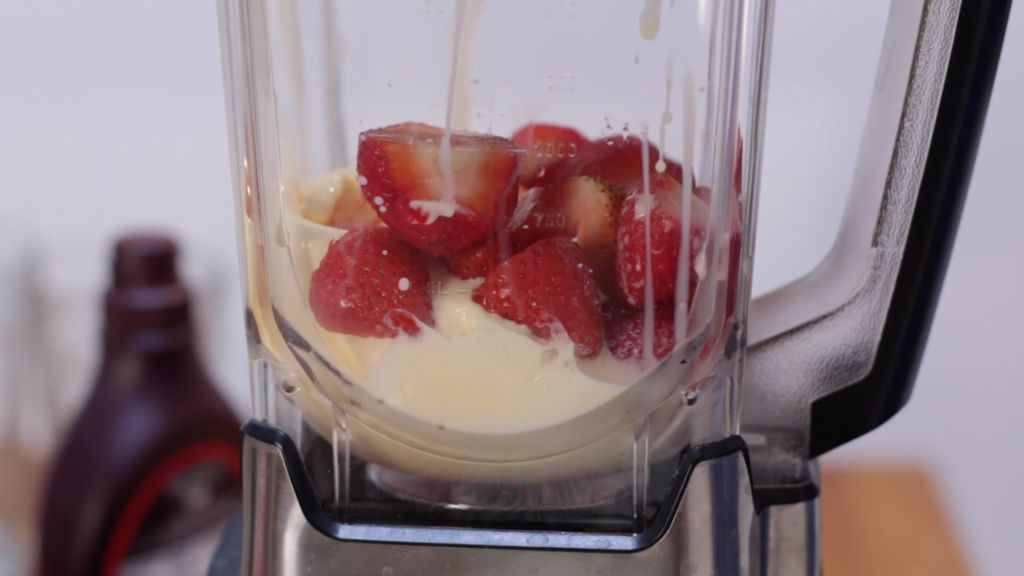 Strawberries, vanilla ice cream, milk, and strawberry syrup in a blender.