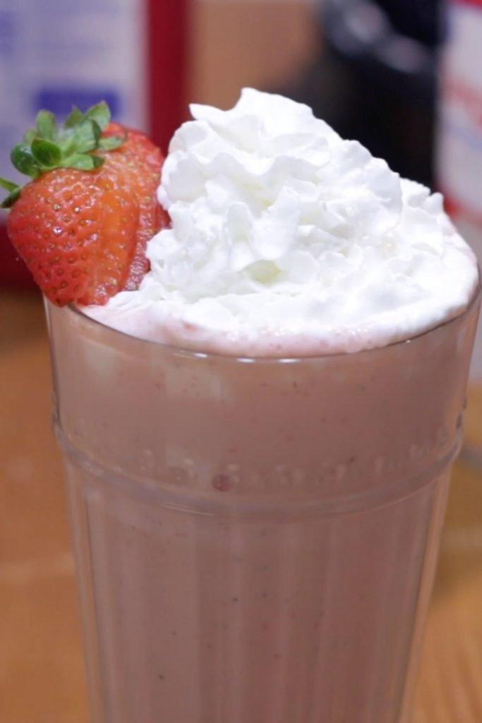 Homemade strawberry milkshake on a wooden table.