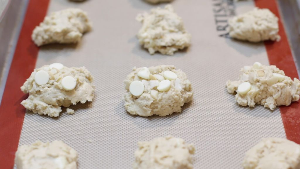Little mounds of white chocolate macadamia nut cookie dough on a sheet pan with a silicone mat.