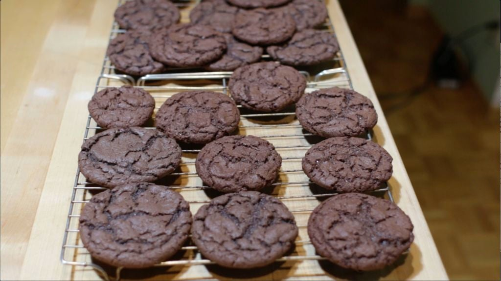 Several chocolate cookies on wire racks.