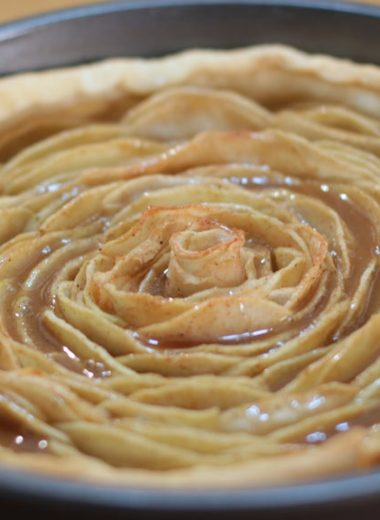 Caramel rose apple pie in a metal pie pan on a wooden table.