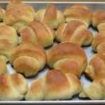 Several soft dinner rolls on a sheet pan.
