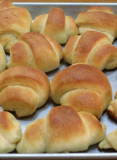 Several soft dinner rolls on a sheet pan.
