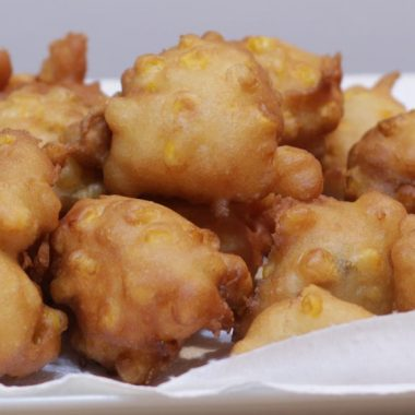 Homemade corn fritters pile up on a plate with paper towel.