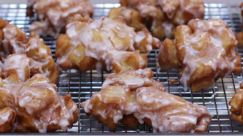 Apple fritters on a wire rack.