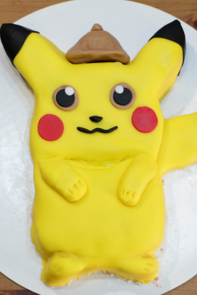 Awesome finished Pokemon Detective pikachu cake on a white cake board.